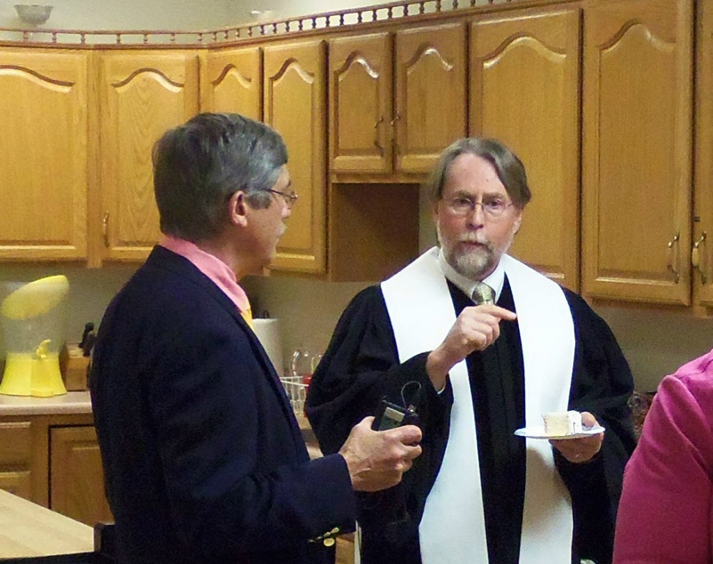 Pastor Phillip and Don Kirk talk in the kitchen.