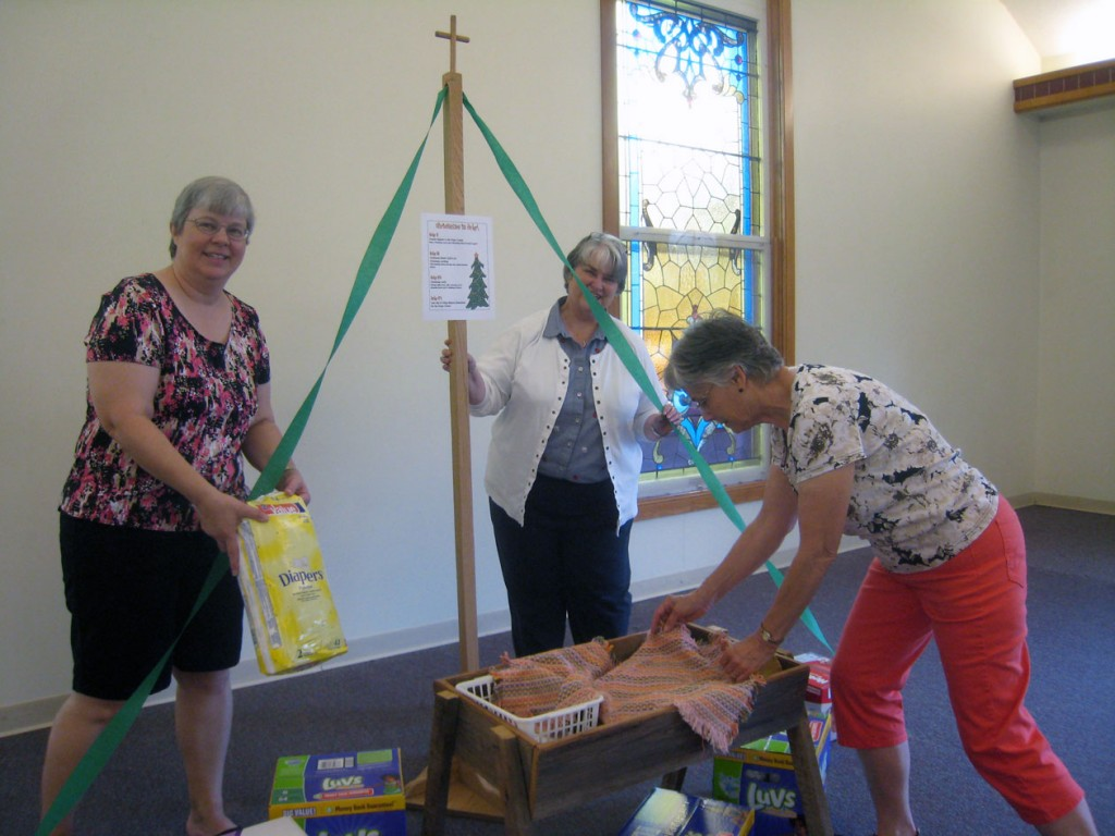 Lisa, Pastor Judy, and Cathy prepare our Diaper Christmas Tree
