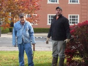 John and Robert trim some shrubs.