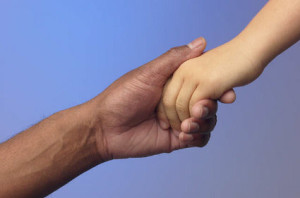 An adult holds a child's hand
