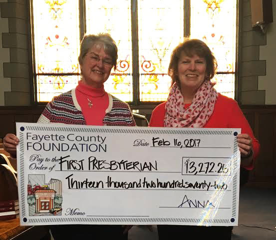 Pastor Judy and Carla Beard display asymbolic check from the Jane and Jerry Wilson Fund.